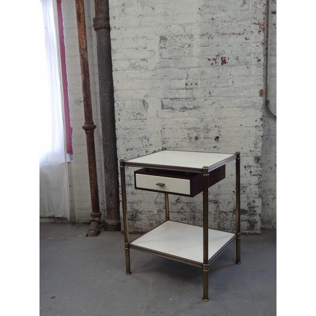 The Cole Porter style side table having two shelves wrapped in parchment and shown with an optional drawer suspended...