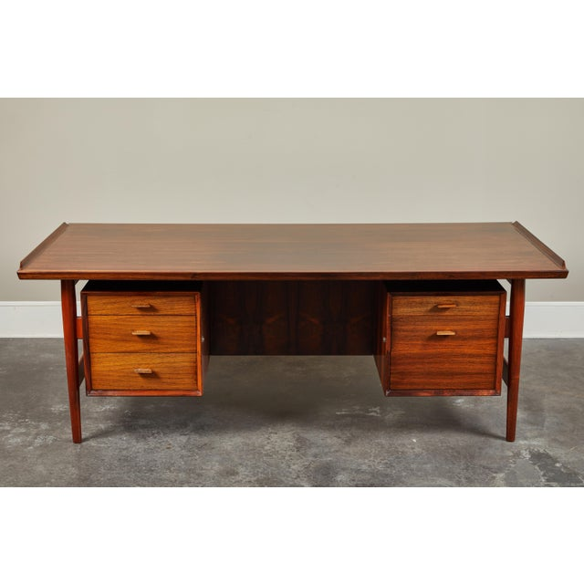 Danish mid-century modern teak desk designed by Arne Vodder. Bold, executive style from every angle.Three drawers on the...