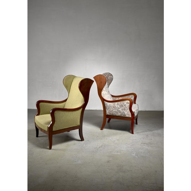 An elegant and comfortable pair of mahogany wingback lounge chairs, by Frits Henningsen. One chair has a lime green and...
