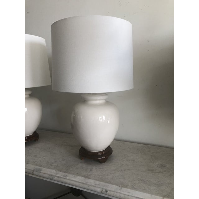 Pair of mid-century white turnip shaped ceramic lamps w/wood base and white drum shades. Perfect side table lamps for...
