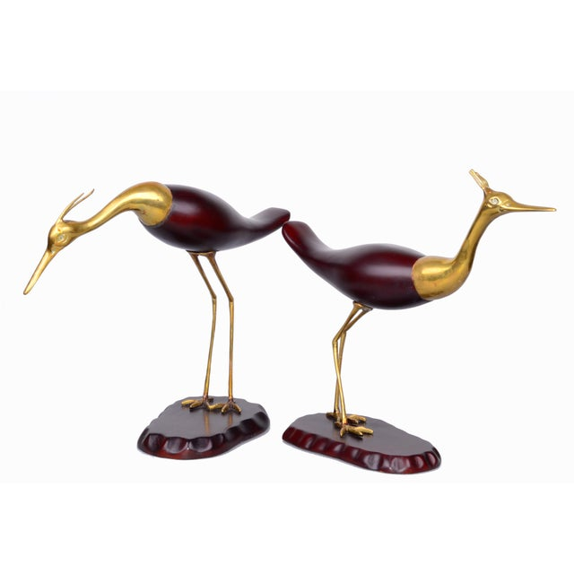 Pair of standing, honed mahogany wood and brass cranes on wood bases.
