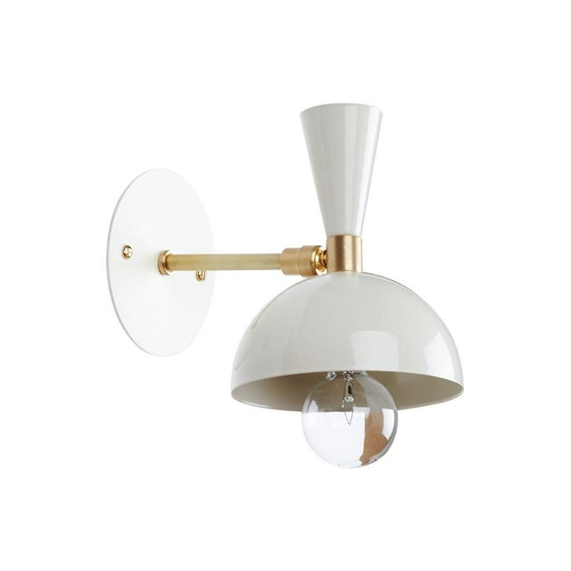 Small contemporary cream-painted metal and brass sconce with a pivoting shade. Recent lighting collaboration by FOCCO X...