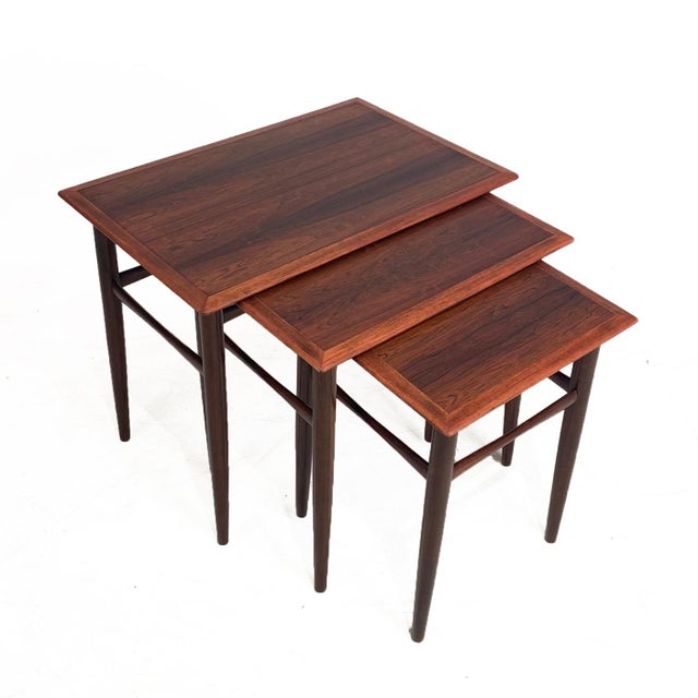 Stunning set of vintage Danish rosewood nesting tables. Each table has beautiful graining on each table top and wonderful...