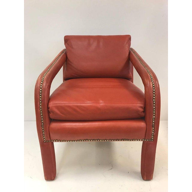 Mid-Century Modern leather lounge chair and ottoman. Chair has slopping arms with brass stud trim to the arms and ottoman.