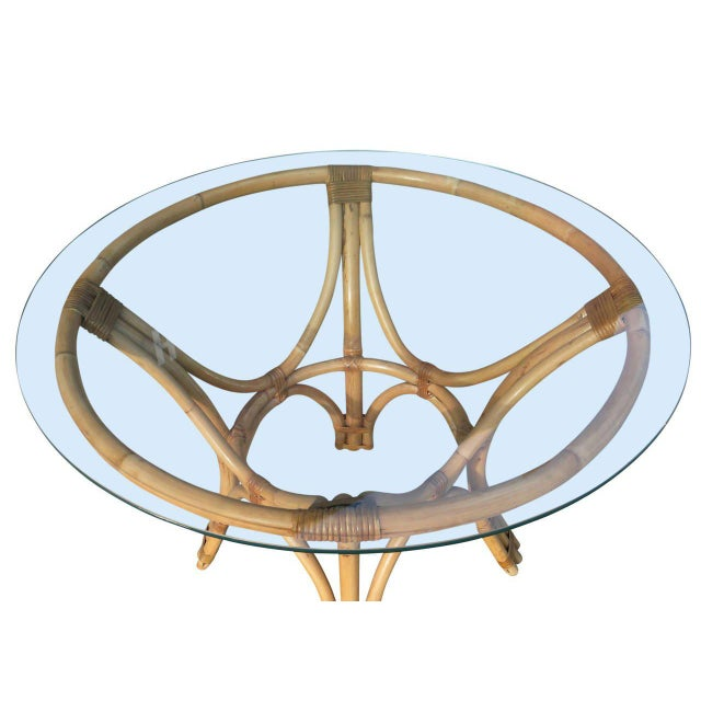 This minimal, yet elegant, dining table features a steam pressed sculptural rattan base with a round glass top. The table...