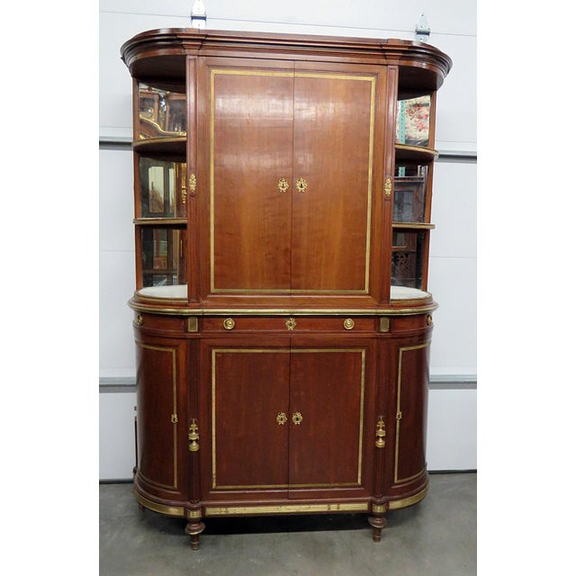 19thC Directoire style china cabinet with bronze mounts. The top has 2 doors containing 2 shelves and 3 open shelves on...