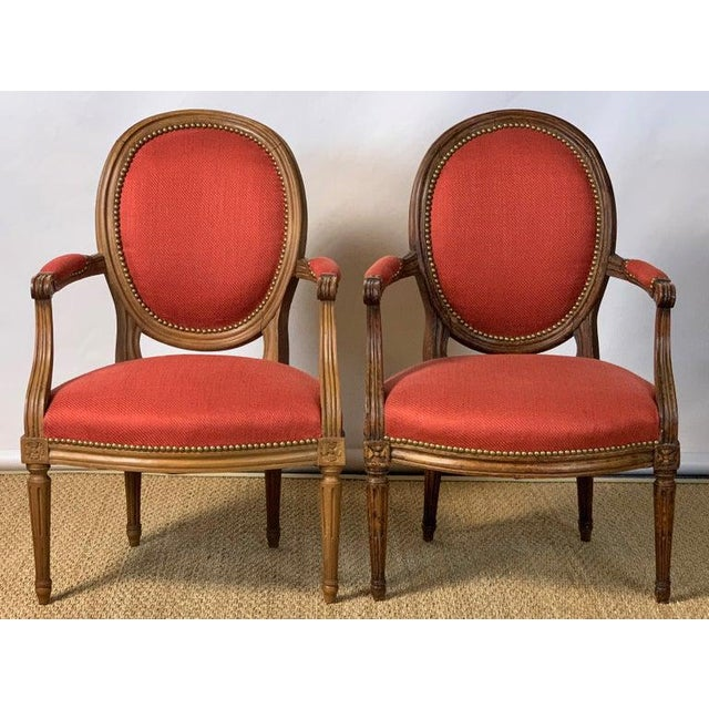 A near pair of French Louis XVI beechwood fauteuils, one dating from the late 18th century, the other made to match some...