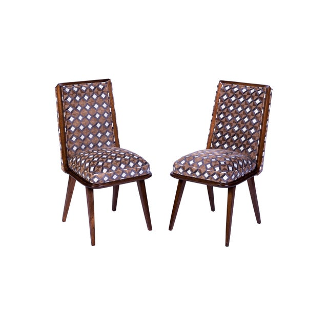 A set of six (6) Mid-Century Modern dining chairs having curved backs and sabre legs, recently upholstered. Made in...