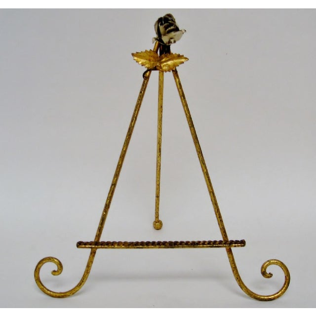 Italian distressed metal easel decorated in a gilded Florentine finish and enameled ivory rose with gold leaves. Tag on...