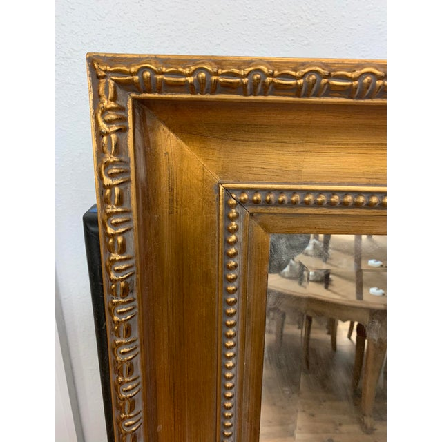 This oversized mirror will make a statement in and home, office or business. The gold frame features details reminiscent...