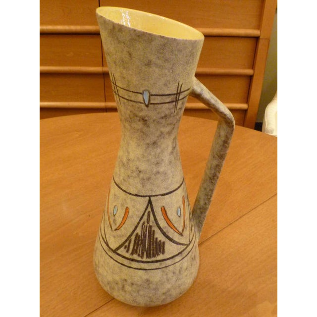 Foamy lava glaze with sgafritto like glazed geometric design sets this 50s ewer form vase apart. A canted shape top and...