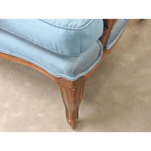 This is a great bergere. Bergere has a carved frame with blue upholstery. Upholstery has light wear and soiling. This is...