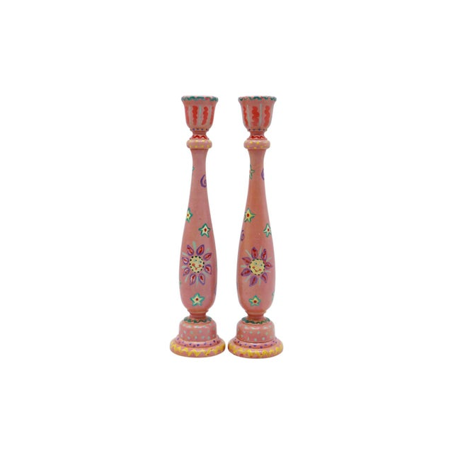 A pair of traditional wooden candlesticks. Simply turned balusters have sleek silhouettes and are hand painted in pink...