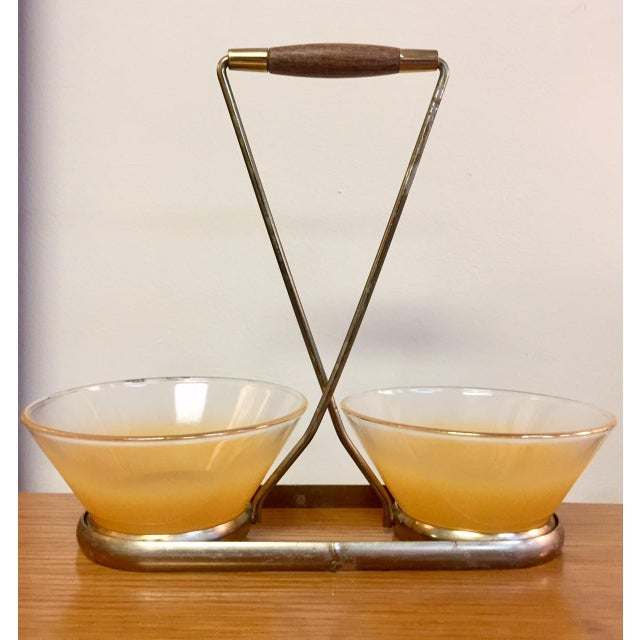 Sweet duo of petite yellow glass bowls in a brass and walnut carrier. This piece is sure to charm your guests while...