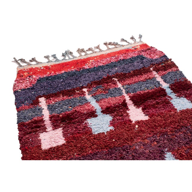 This charming Moroccan rug is lively and fun. A relaxed mix of red, pink, blue and purple in a confetti-like texture. Hand...