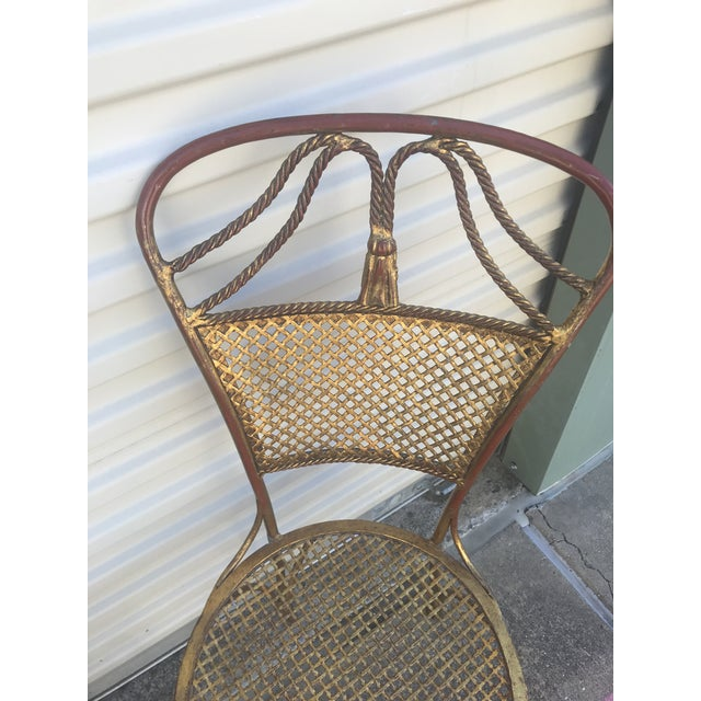 Italian metal petite golden chair. Metal cane seat and rope and tassel details.