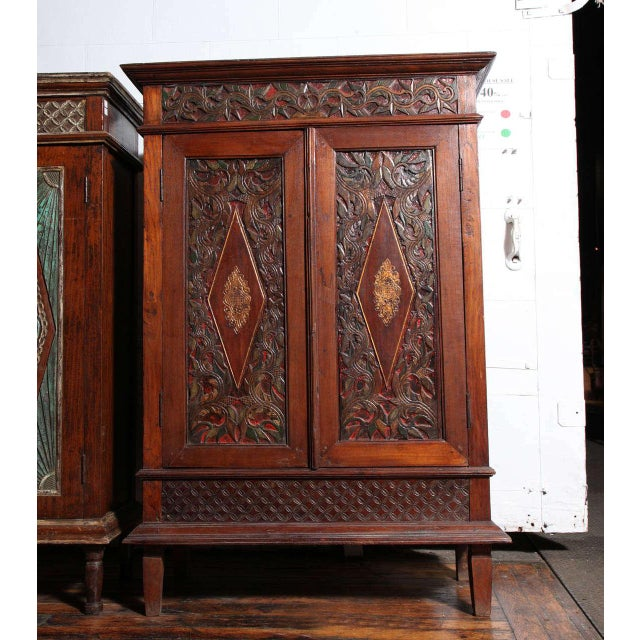 An early 20th century cabinet with detailed carved teak wood from Java, Indonesia. This cabinet adopts a rectangular shape...