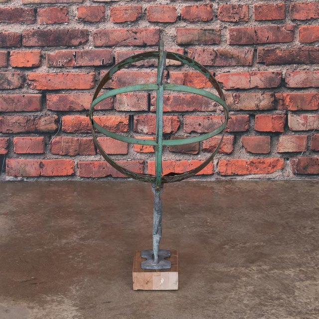 This vintage globe shaped garden ornament, called an armillary, is made up of metal bands pierced by an arrow and...