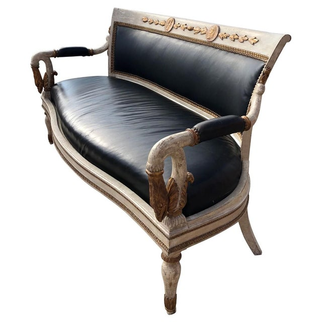 Created in the regal Empire style in France during the 19th century, this antique settee has a distressed, pale walnut...