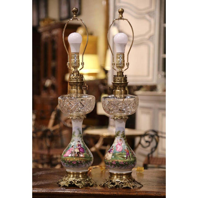 "This elegant pair of antique oil lamps made into table lights was crafted in France, circa 1880. The tall ""lampes a..."