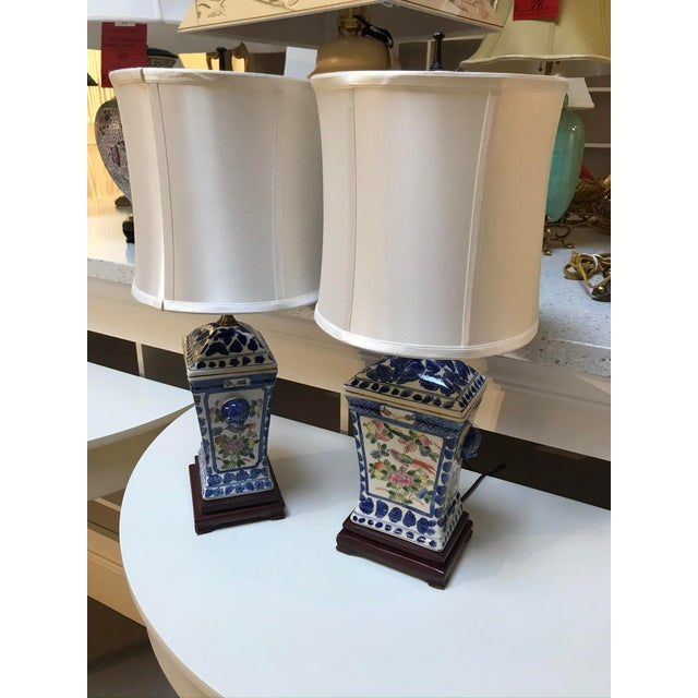 A pair of blue and white porcelain lamps with attached wood bases and complimentary cylindrical silk lamp shades. These...