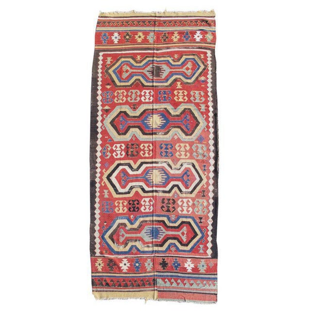 This iconic Konya area kilim draws a field of elongated and highly evocative cartouches against a madder-red ground with...