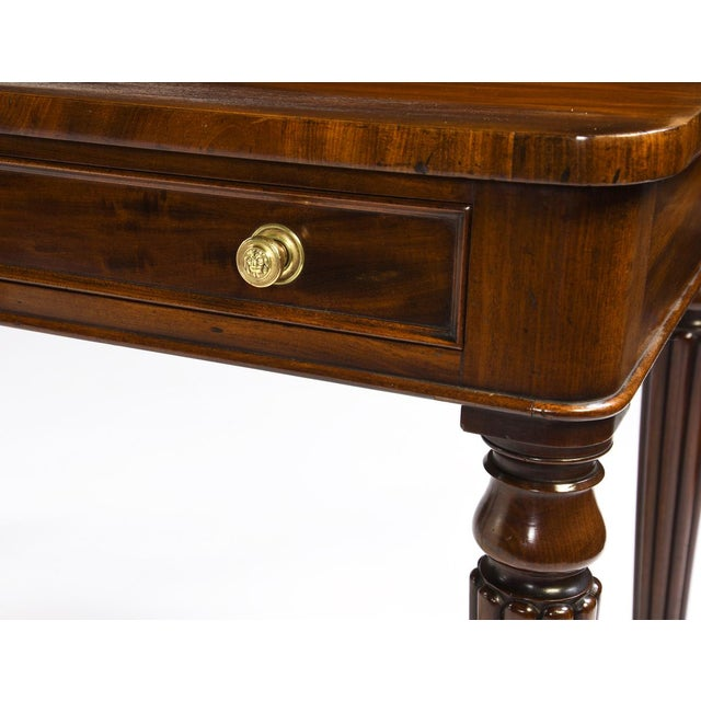 Antique English Regency mahogany two drawer writing table with small wooden gallery with carved roundels. It has a...