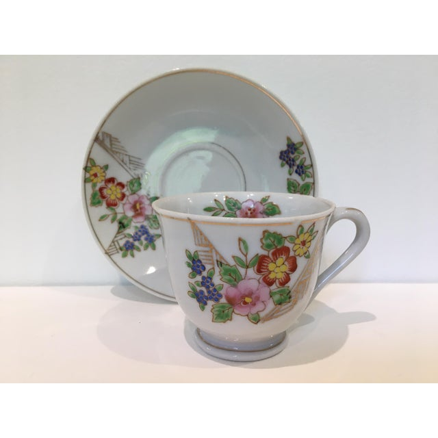 Charming teacup and four matching saucers with delicate gold outlines and hand-applied color. Saucer shapes are ever-so-...