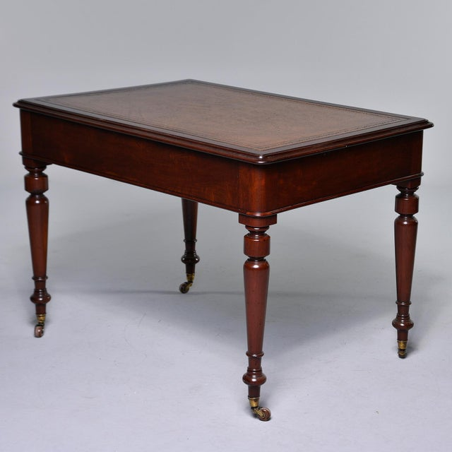 Circa 1880s English writing table / desk is made of mahogany and has a leather top, two functional drawers and turned legs...
