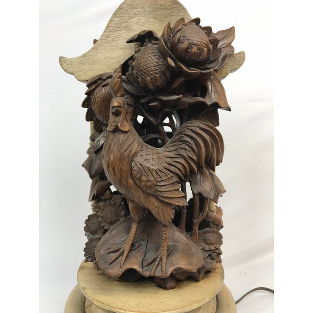 A pair of 19th century French carved wooden cockerels and flowers mounted upon a mid 20th century lamp base. Top of lamp...