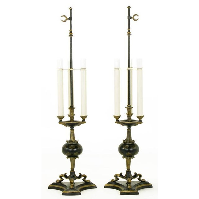 Extremely well-constructed Empire style table lamps of black lacquered metal with parcel gilt detailing. Triple lions paw...