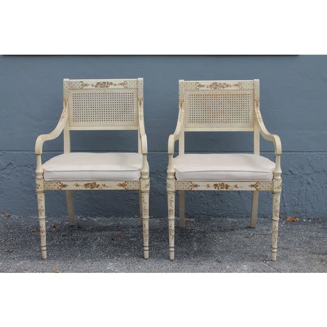 A beautiful pair of mid century gilt decorated/ faux bamboo/ caned/ off white armchairs. Perfect for a French style lounge...