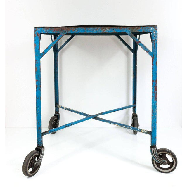 Unusual industrial table on heavy elevated casters. The iron frame has traces of blue painted patina, French, 1920s.