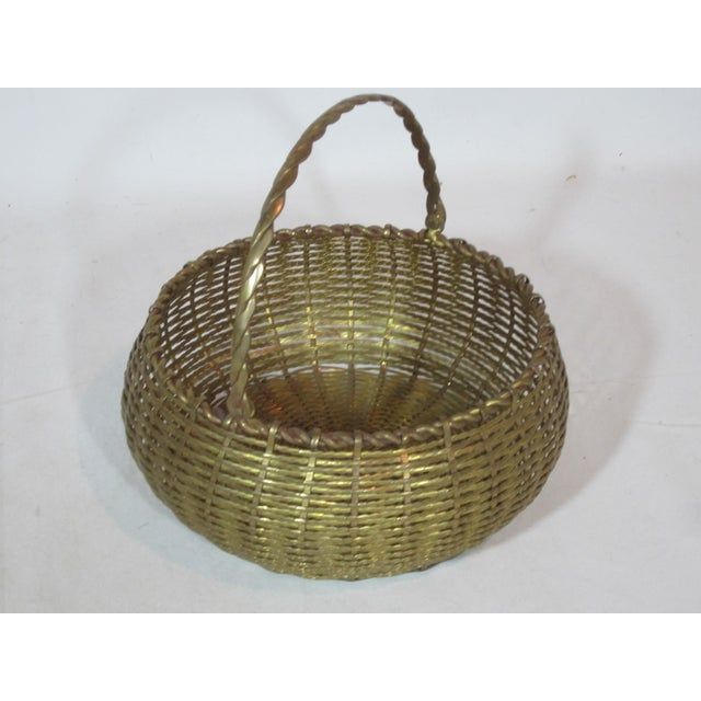 This is a round bombay shaped, solid brass woven basket with swing handle.