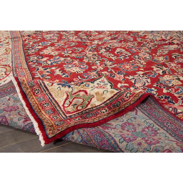 A hand-knotted Tabriz rug with a floral medallion design on a red field. This amazing vintage rug is perfect for any style...