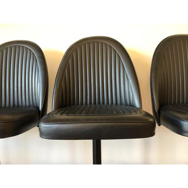 In good vintage condition. Stools are upholstered in black naugahyde with a sturdy, metal base foot rest. No stains,...