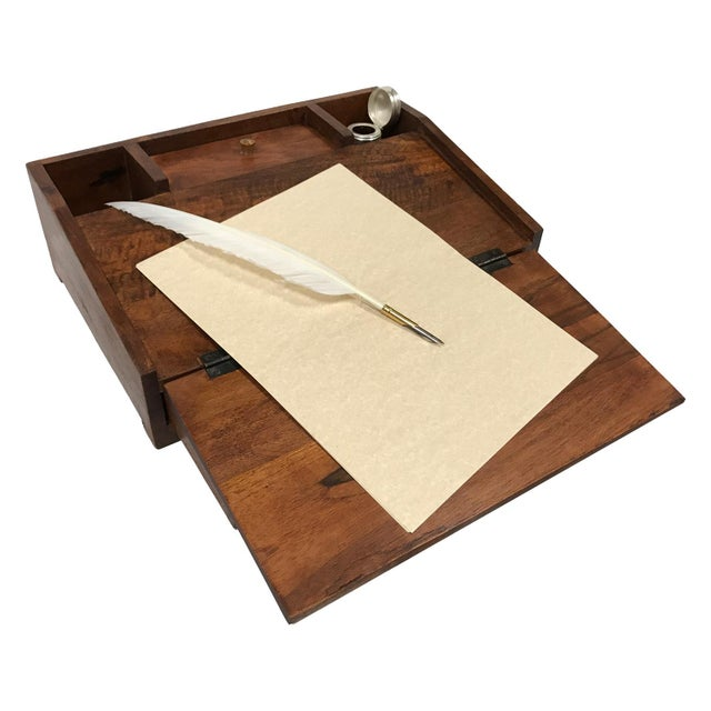 With a two smaller open compartments for ink wells, a larger compartment with lid, a fold out top lid creating the writing...