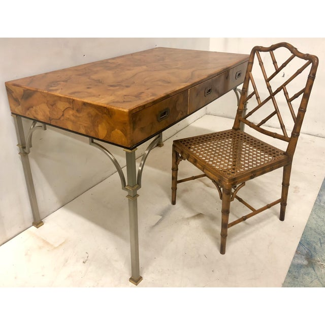 1970s olive burlwood campaign style desk with faux bamboo chair. The desk is Italian and has a steel and brass base. The...