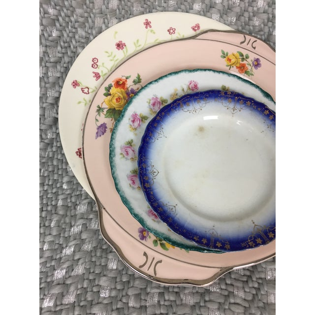 A cute set of 4 mismatched ceramic china plates featuring floral patterns. Colors range from light pink to deep navy blue....