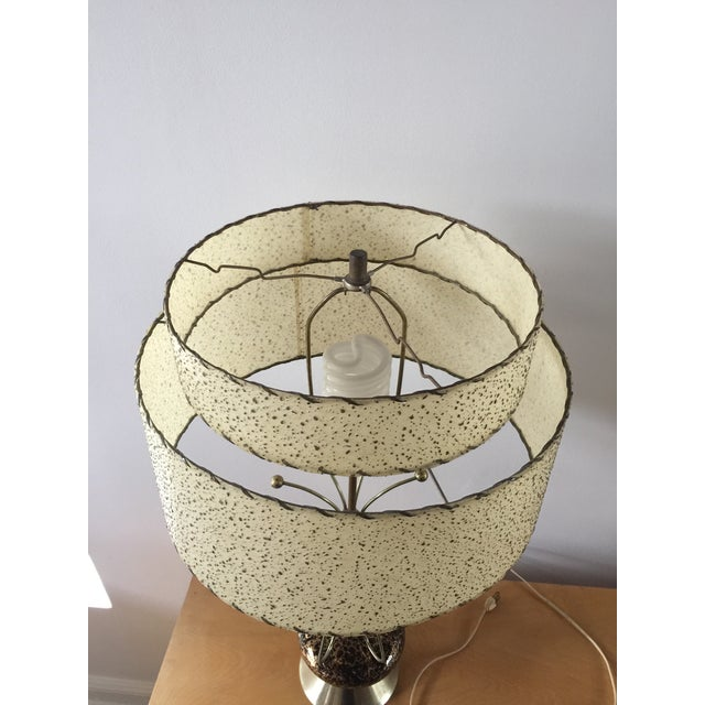 Fun retro atomic age table lamp! Ceramic black base with a gold/brass tone crackle pattern. There is a section that does...