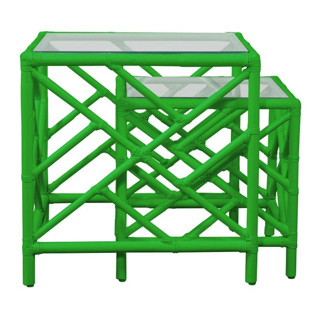 In a classic chinoiserie style, this set of two rattan nesting tables feature a rattan frame, rawhide bindings, hand...