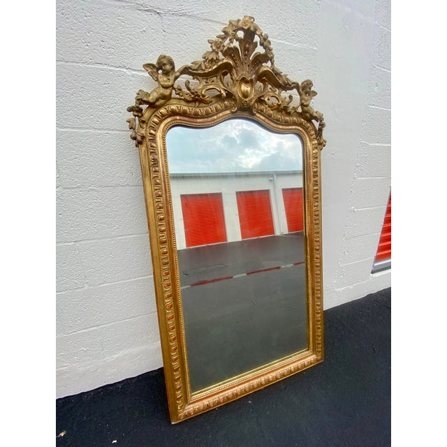 Exquisite French Louis Style gilt carved wood wall mirror with centered floral, crest medallion, flanking cherubs perched...