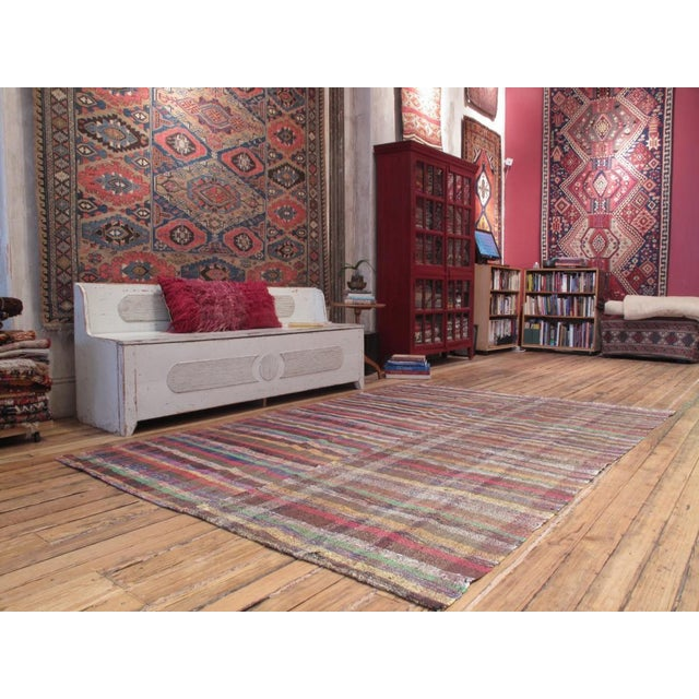 A simple, old tribal floor cover, made for everyday use, with a lively, surprising color palette. The weaving technique...
