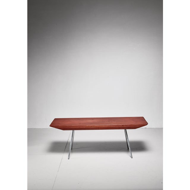 A rectangular coffee or side table, made of a thick stained pine top with thin aluminum legs. The table was made by...