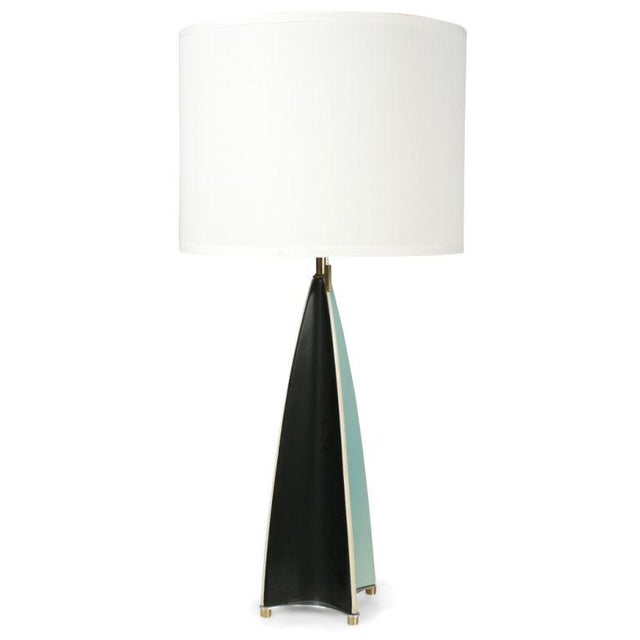 A mod table lamp in an elongated parabolic form with concave sides in a pattern of alternating aqua and dark grey glaze....
