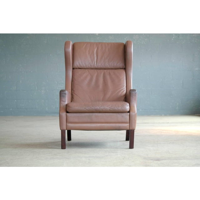 Georg Thams wingback chair in cappuccino colored leather. Made in the 1960s or early 1970s and very much in the style of...