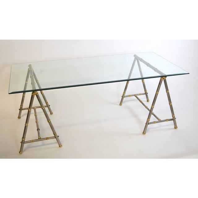 A chic pair of steel trestle or sawhorse form coffee table bases with brass accents. Stylized faux bamboo after Maison...