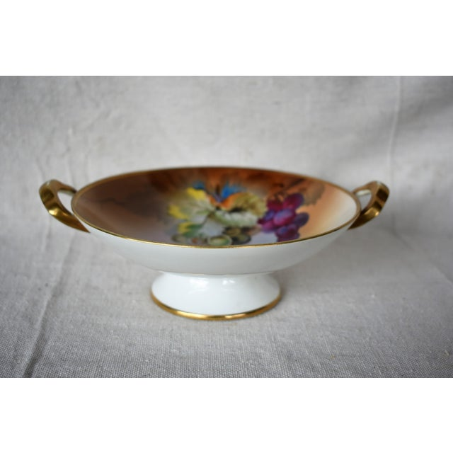 """A vintage hand painted two handled Japanese bowl marked """"Nippon"""" showing two bunches of grapes. The colors are vibrant and..."""