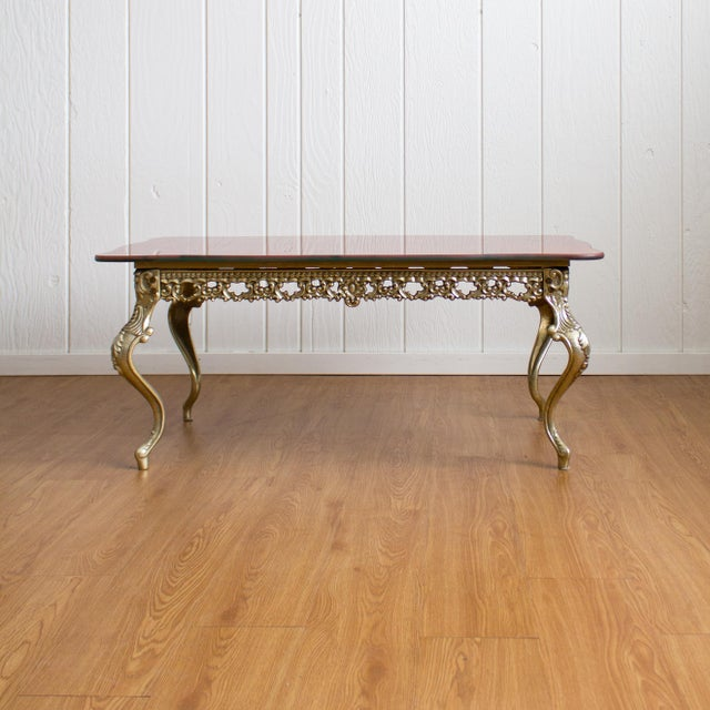 Hollywood Regency coffee table features cabriole brass legs with a thick scalloped glass top that features faux marbling...