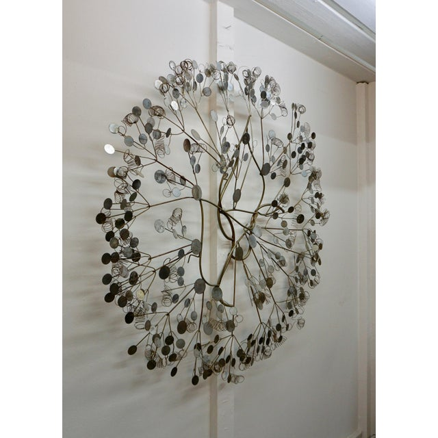 "Whimsical,wall mounted sculpture consisting of chrome plated steel discs welded to chrome plated rods. 43"" in diameter."